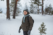 Portrait attractive man in winter pine forest. He clothed in dark green jacket, gray striped scarf, hat and gloves.