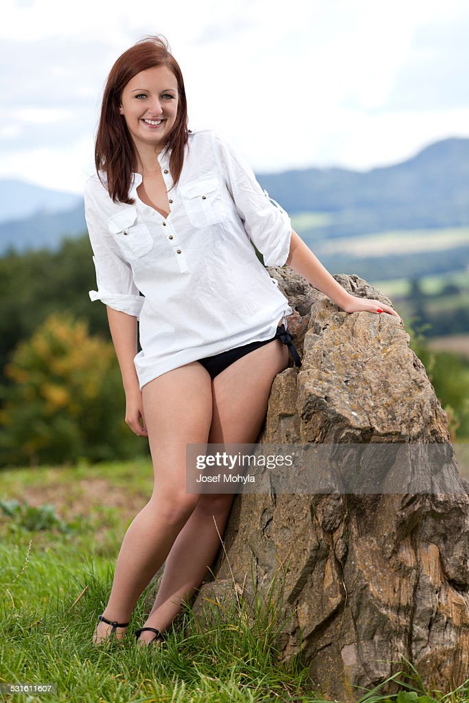 Portrait attractive woman beside big stone