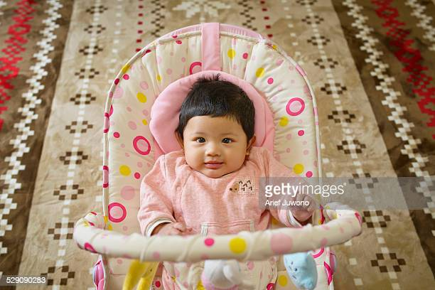 A Portrait baby cute sitting in her baby bouncer