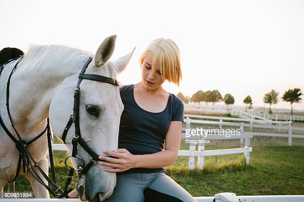 portrait: blonde teenager girl with her white horse outdoors