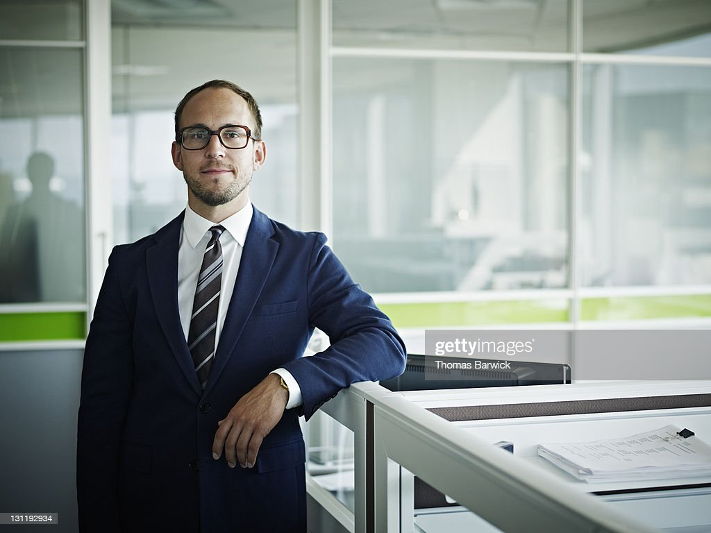 Portrait businessman resting arm on workstation : Stock Photo