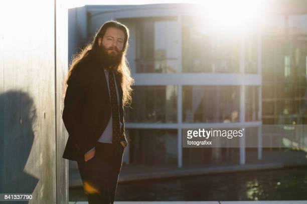 Portrait: businessman with long hair and beard, back lit, rebellion