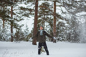 Portrait cheerful man in winter pine forest. He blowing snow up from gloves in winter day.