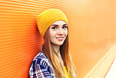Portrait closeup beautiful young girl in yellow hat over colorful background