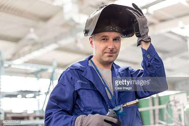 Portrait confident welder with welding torch in factory