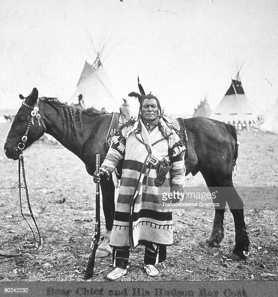 Portrait entitled 'Bear Chief and His Hudson Bay Coat' depicts a Piegan Blackfoot as he stands rifle at his side before his horse in a campsite...