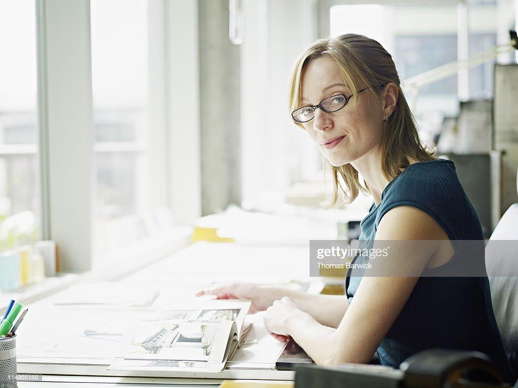 Portrait female architect at desk : Stock Photo