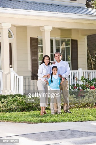 Portrait happy Hispanic family standing in front of house