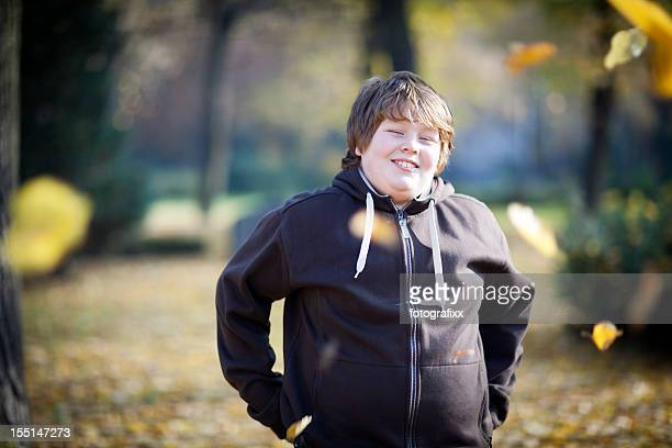 portrait: laughing overweight boy on nature background, looking at camera