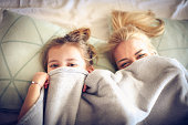 Portrait mother and daughter hide under blanket on a bed.