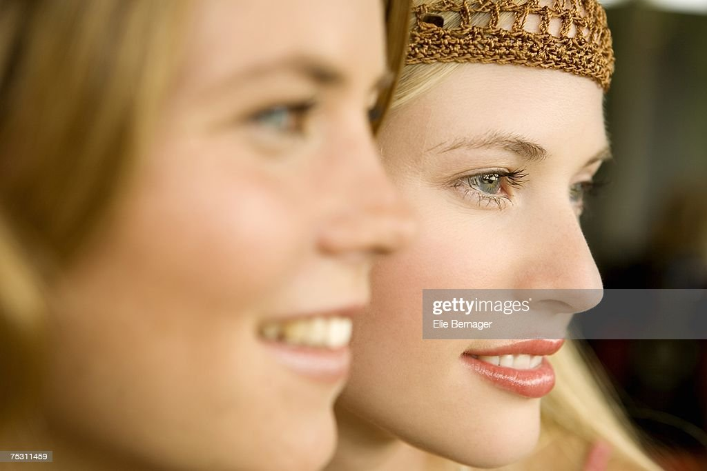 Portrait of 2 young smiling women, view in profile : Stock Photo