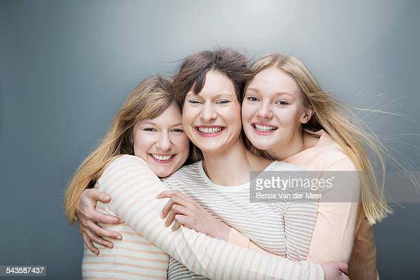 Portrait of 3 sisters embracing and  laughing.