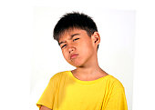 portrait of 7 or 8 years old kid in serious and cool face expression posing as a badass playing the bully isolated on white background wearing yellow tshirt in interesting child face expression concep