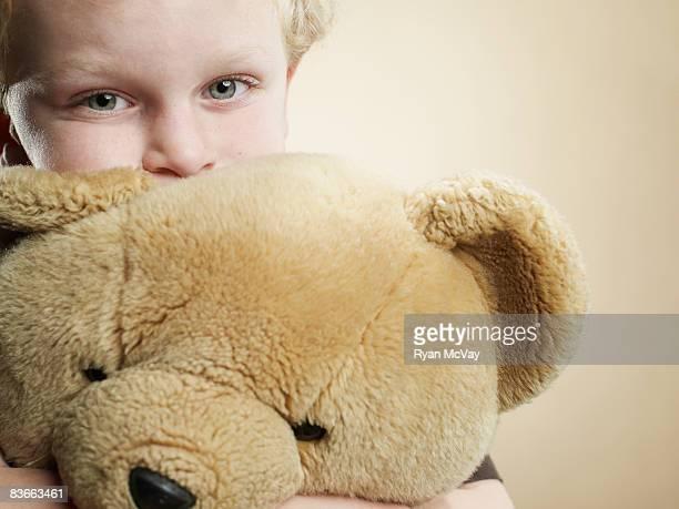 Portrait d'un garçon de 6 ans ours en peluche près