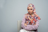 Image of a angry young Malay woman wearing a hijab frowning with arms crossed.