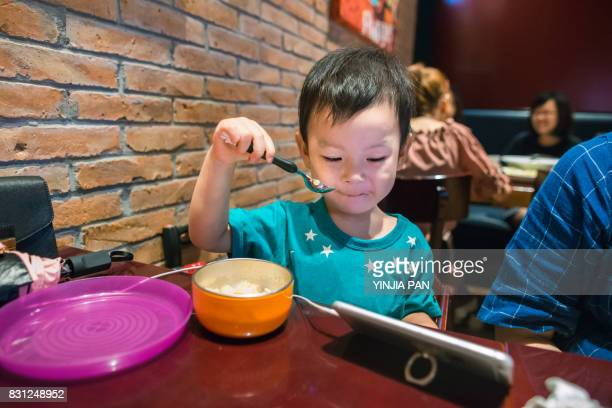 Portrait of a baby boy eating rice with a spoon in restaurant