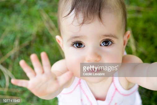 Portrait of a baby girl with arms raised : Stock Photo