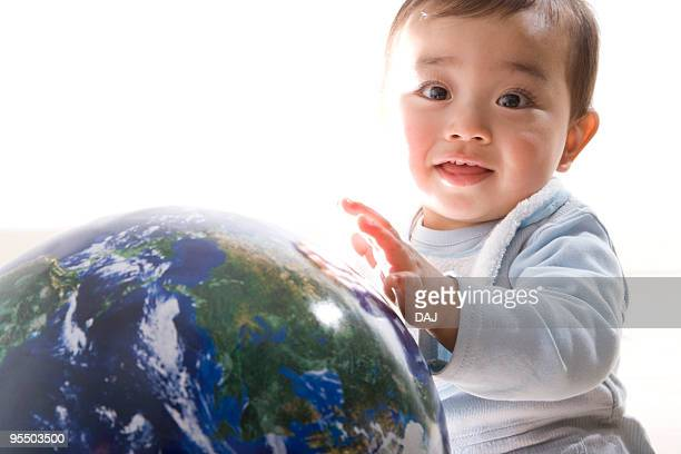 Portrait of a baby holding a globe, smiling, white background