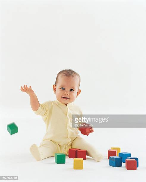 Portrait of a Baby in a Romper Suit Playing With Wooden Blocks