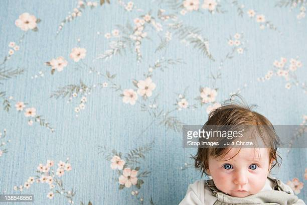 Portrait of a baby in front of floral wallpaper