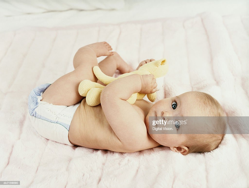 Portrait of a Baby Lying on a Bed : Stock Photo