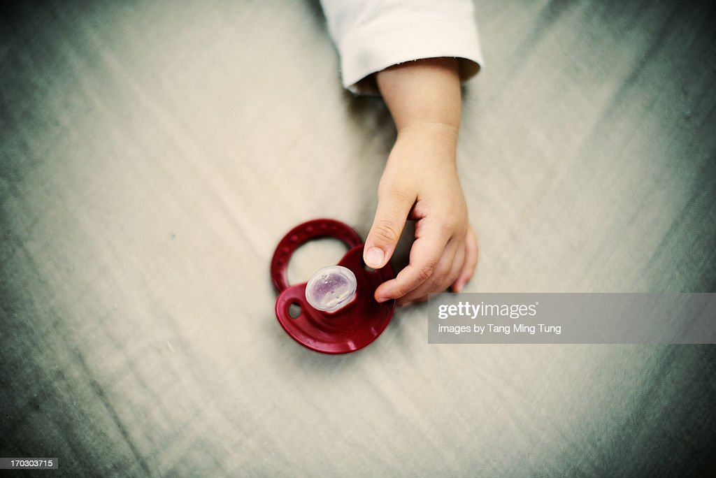 A portrait of a baby's hand with a pacifier : Stock Photo