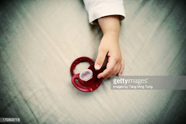 A portrait of a baby's hand with a pacifier