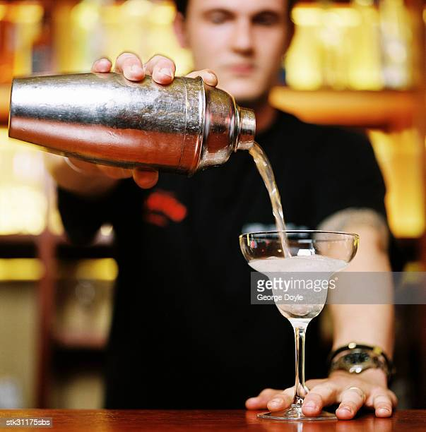 portrait of a bartender pouring a cocktail from a shaker