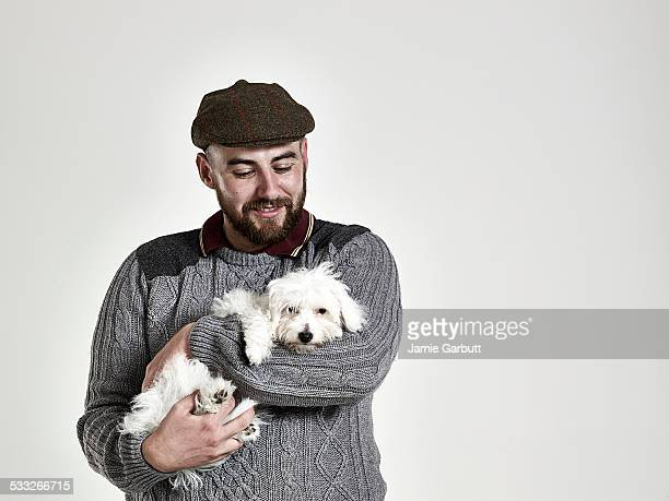 Portrait of a bearded male happily holding a puppy