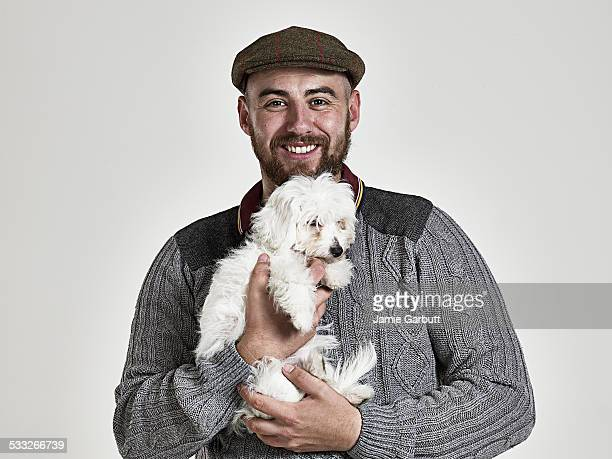 Portrait of a bearded male holding a puppy