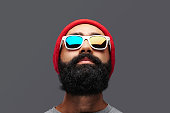 Portrait of bearded male with a red cap and colorful glare in sunglasses.