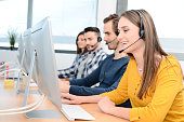 portrait of a beautiful and cheerful young woman telephone operator with headset working on desktop computer in row in a customer service call support helpline business center with teamworker in backg
