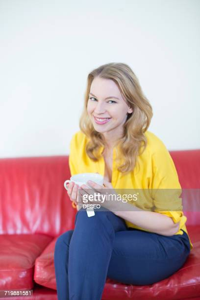 Portrait of a beautiful blonde woman enjoying a cup of tea on the sofa and smiling at camera