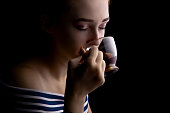 portrait of a beautiful girl with makeup drinking tea, woman's face with eyes closed on a black background