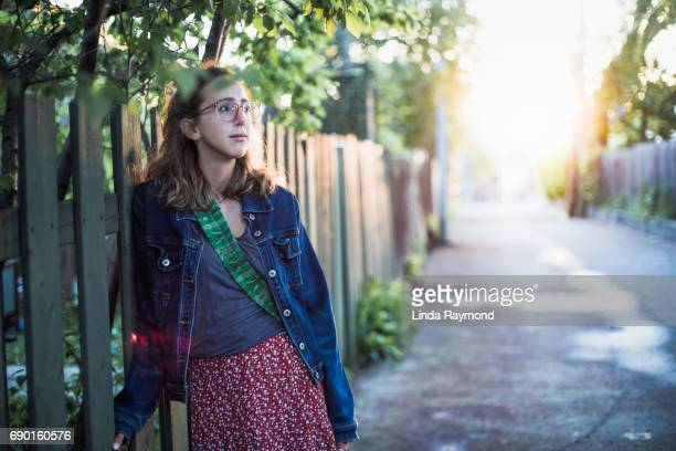 Portrait of a beautiful girl wearing glasses in an alley at sunset