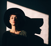 Portrait of a beautiful female with hat. Poetic portrait with hard shadow