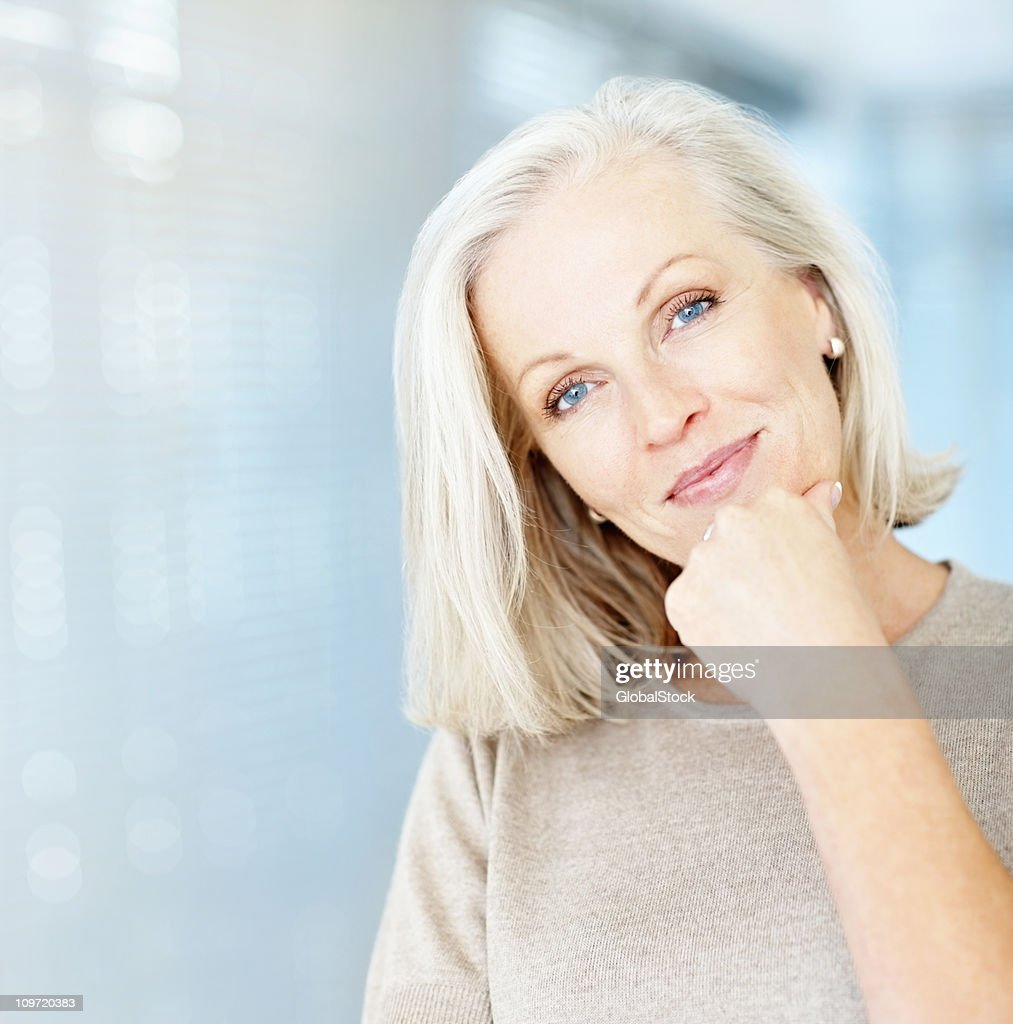 Portrait of a beautiful mature woman with hand on chin : Stock Photo