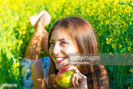 Portrait of a beautiful smiling woman with an apple : Stockfoto