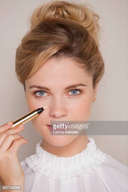 Portrait of a beautiful woman applying concealer