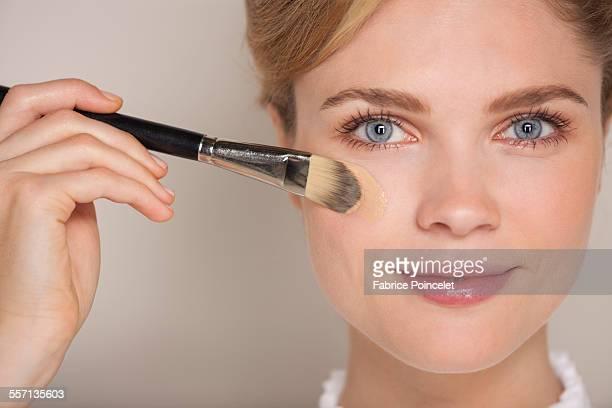 Portrait of a beautiful woman applying foundation