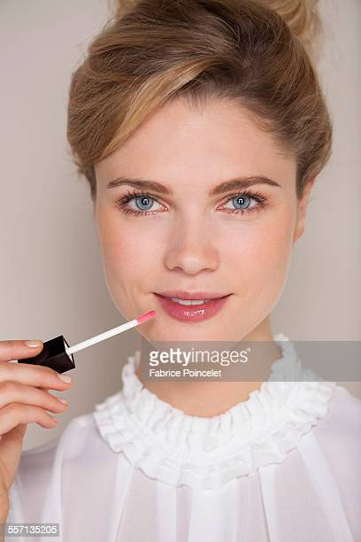 Portrait of a beautiful woman applying lip gloss