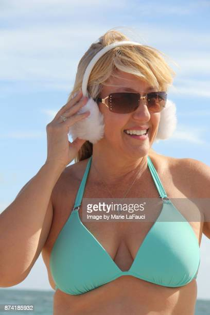 Portrait of a beautiful woman at the beach wearing earmuffs