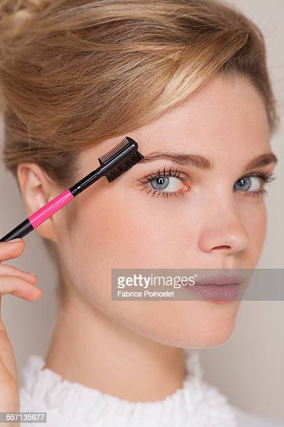 Portrait of a beautiful woman brushing her eyebrow