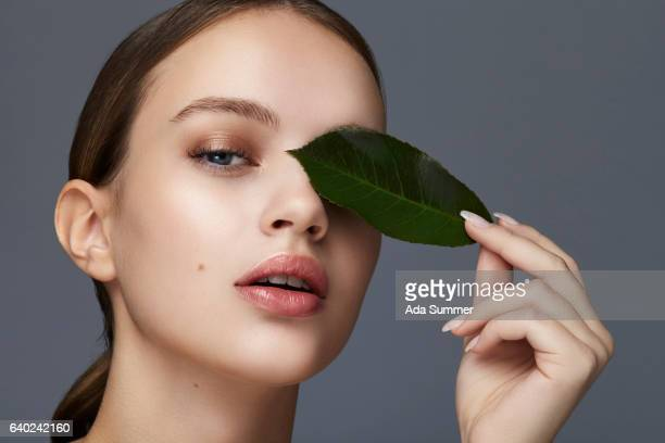 Portrait of a beautiful  woman covering on eye with a green leaf