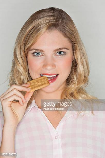 Portrait of a beautiful woman eating a biscuit