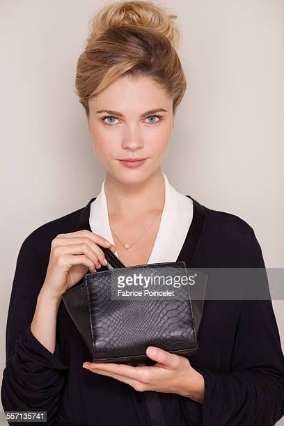 Portrait of a beautiful woman holding makeup bag