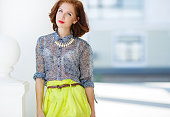 Fashion woman with brown hair and stylish hair,gray eyes and red lipstick,dressed in lemon-colored skirt and gray blouse,wears a white necklace,red nail Polish,posing on the street in the city in the