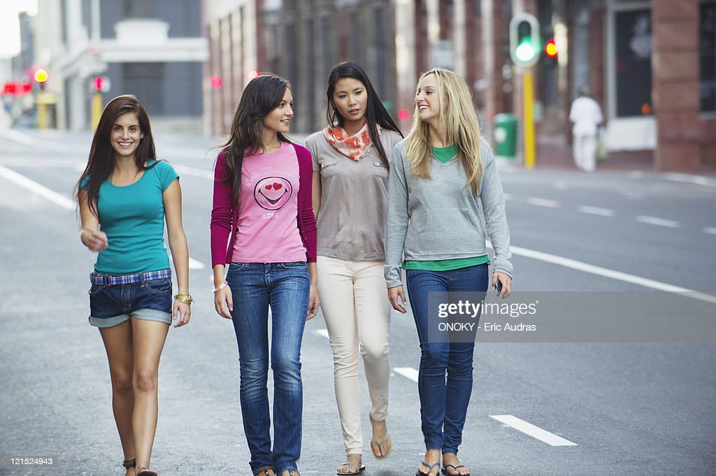 Portrait of a beautiful woman walking with friends on the road : Stock Photo