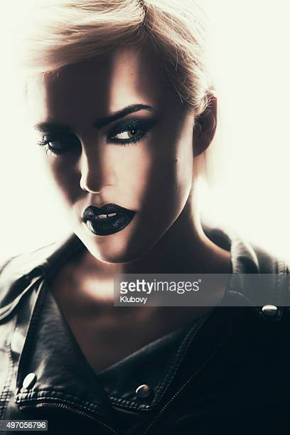 Portrait of a beautiful woman with a strong dark makeup.