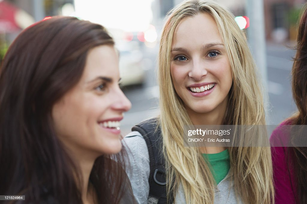 Portrait of a beautiful woman with friends outdoors : Stock Photo